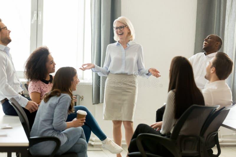 Kvinnlig affärslagledareledare och lagfolk som skrattar på utbildning royaltyfri bild