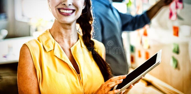 Kvinnlig affärsledare som rymmer den digitala minnestavlan royaltyfri bild