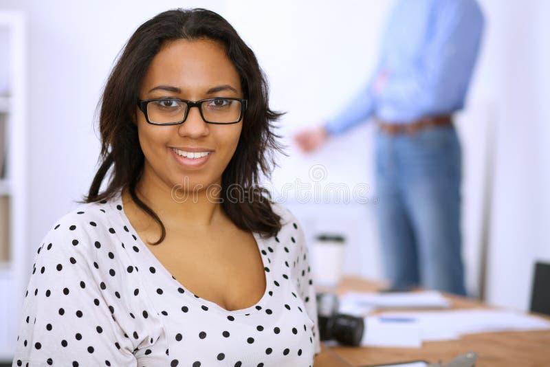 Kvinnlig afrikansk amerikan på mötet eller idékläckning Begrepp av ett ungt lag av affärsfolk eller studenter royaltyfri foto