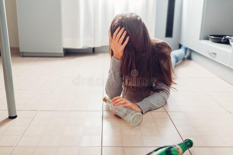 Kvinnlig alkoholböjelse Den unga kvinnan vaknade upp på kökgolv efter partiet som omgavs med vinflaskor bakrus royaltyfria bilder