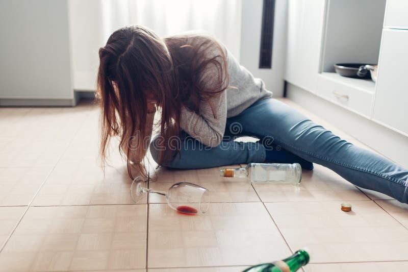 Kvinnlig alkoholböjelse Den unga kvinnan vaknade upp på kökgolv efter partiet som omgavs med vinflaskor bakrus fotografering för bildbyråer