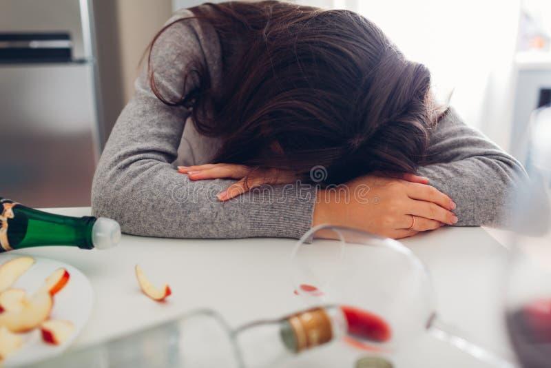 Kvinnlig alkoholböjelse Ung kvinna som sover på köksbordet som omges med vinflaskor arkivbilder