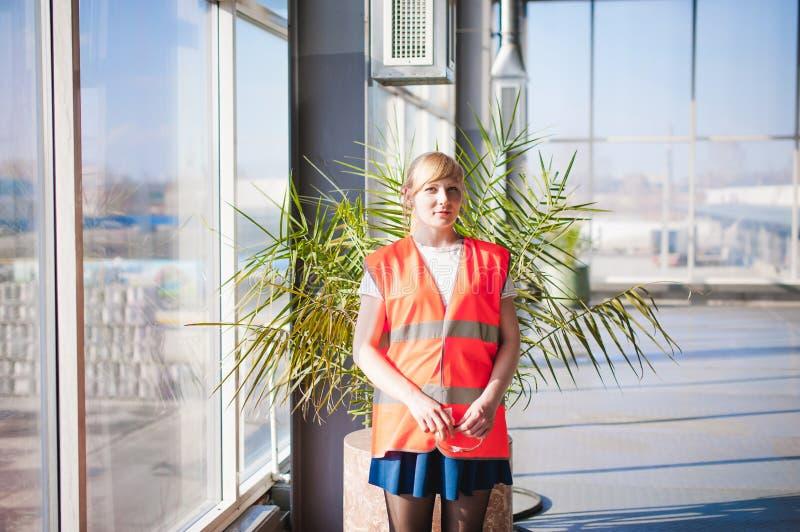 Kvinnlig anställd i orange bära för ämbetsdräkt tilldelar produktionrum för funktionsdugligt utrymme, mot stora fönster för bakgr royaltyfri foto