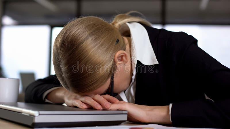 Kvinnlig anställd som ligger på bärbara datorn som förargas med arbete, nervsammanbrott, spänning royaltyfri foto