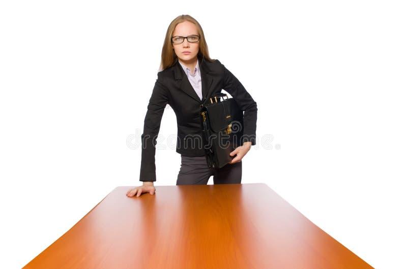 Kvinnlig anst?lld som sitter p? den isolerade l?nga tabellen p? vit royaltyfri bild