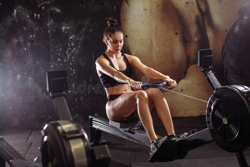 Kvinnlig användande roddmaskin i idrottshall kvinna som gör cardio genomkörare i konditionklubba arkivfoton
