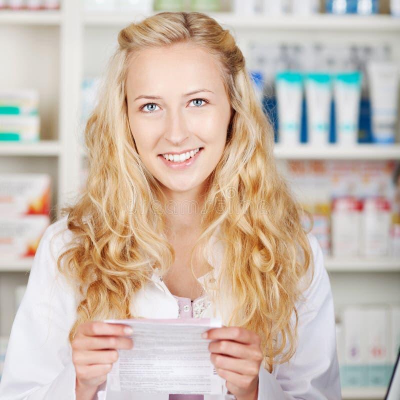 Kvinnlig apotekare Holding Prescription Paper royaltyfria foton