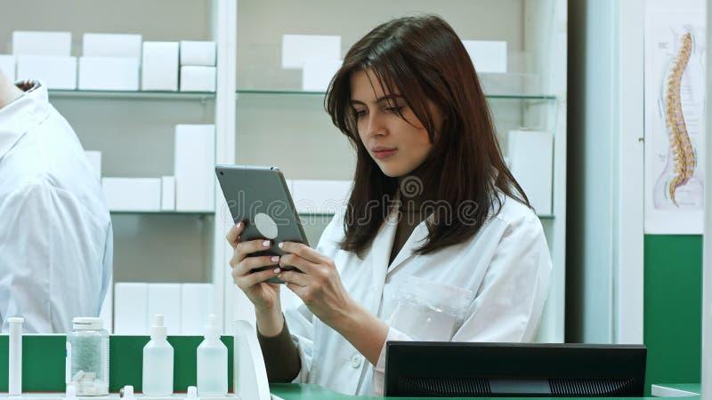 Kvinnlig apotekare med den digitala minnestavlan som söker för läkarbehandling arkivbilder