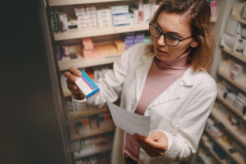 Kvinnlig apotekare med receptet som kontrollerar medicin royaltyfri fotografi