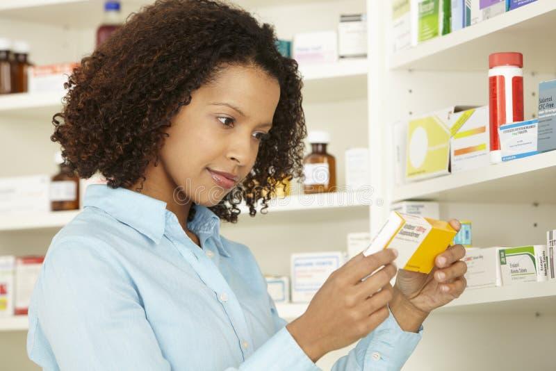 Kvinnlig apotekare som arbetar i UK-apotek arkivfoto
