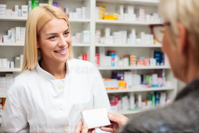 Kvinnlig apotekare som förklarar terapidetaljer till den höga kvinnliga patienten arkivbild