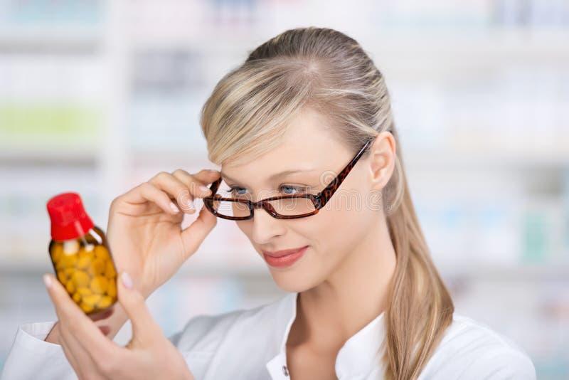 Kvinnlig apotekare som läser medicinetiketten royaltyfri bild