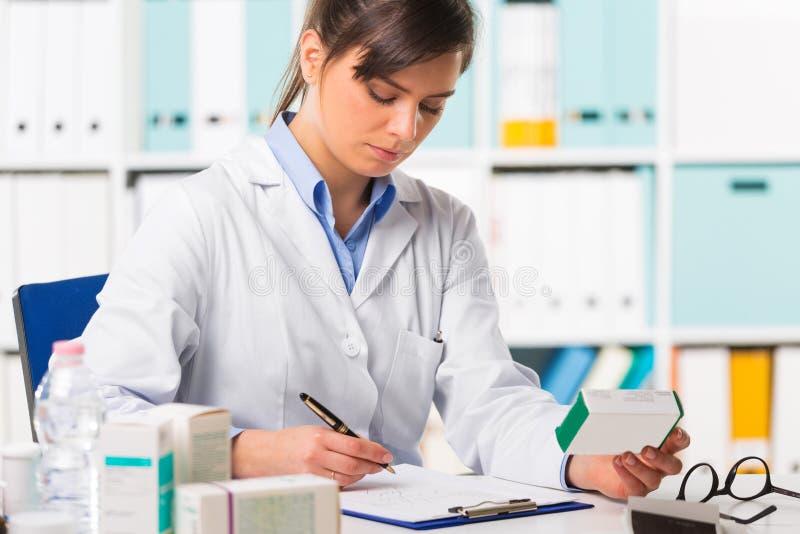 Kvinnlig apotekare som sitts på skrivbordhandstilanmärkningar royaltyfria bilder