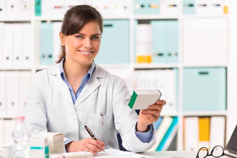 Kvinnlig apotekare som sitts på skrivbordhandstilanmärkningar arkivfoto