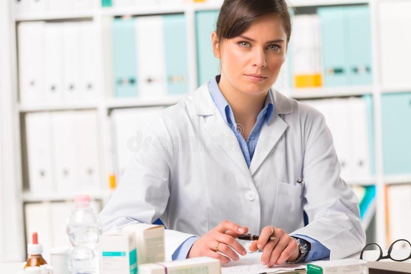 Kvinnlig apotekare som sitts på skrivbordhandstilanmärkningar royaltyfri fotografi