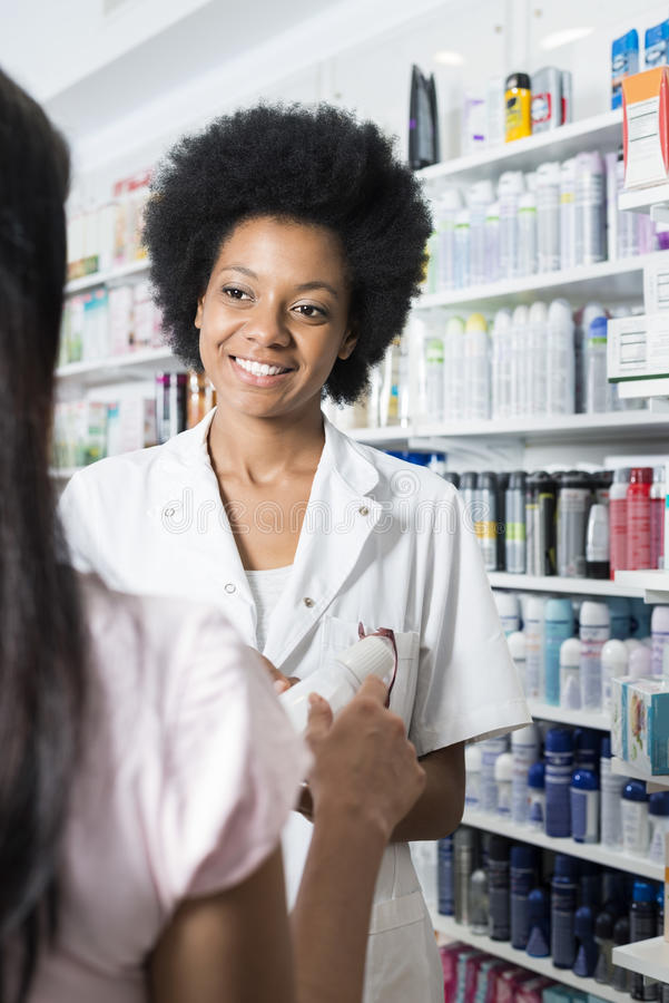 Kvinnlig apotekareShowing Product To kund i apotek fotografering för bildbyråer