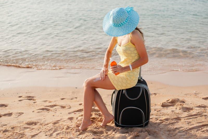 Kvinnlig applicerande solkräm på benet Skincare solskydd Kvinnasudd som fuktar lotionon på hennes släta brunbrända ben arkivbilder