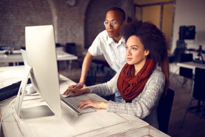 Kvinnlig arbetare med den manliga arbetsledaren på affär på datoren royaltyfria foton
