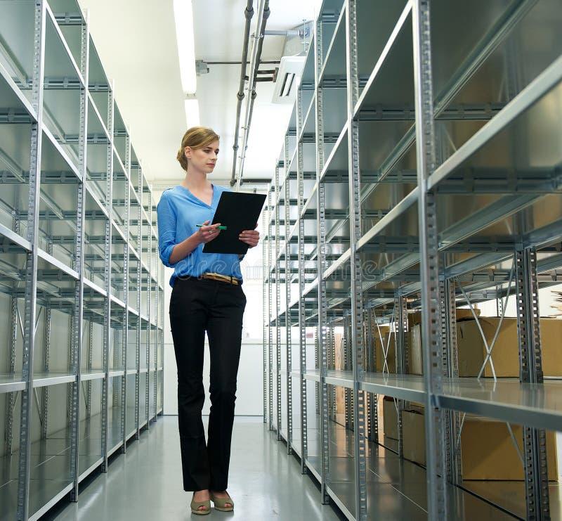 Kvinnlig arbetare med skrivplattan, oraganizing inventarium och materielet i lager arkivfoton