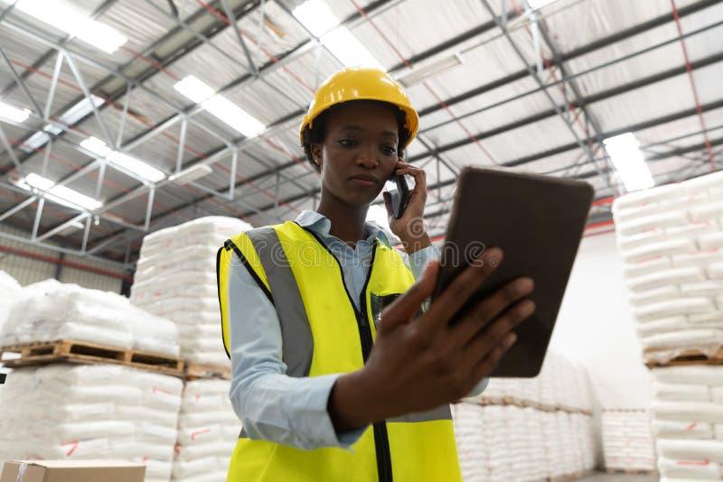 Kvinnlig arbetare som använder den digitala minnestavlan, medan tala på mobiltelefonen i lager arkivbilder