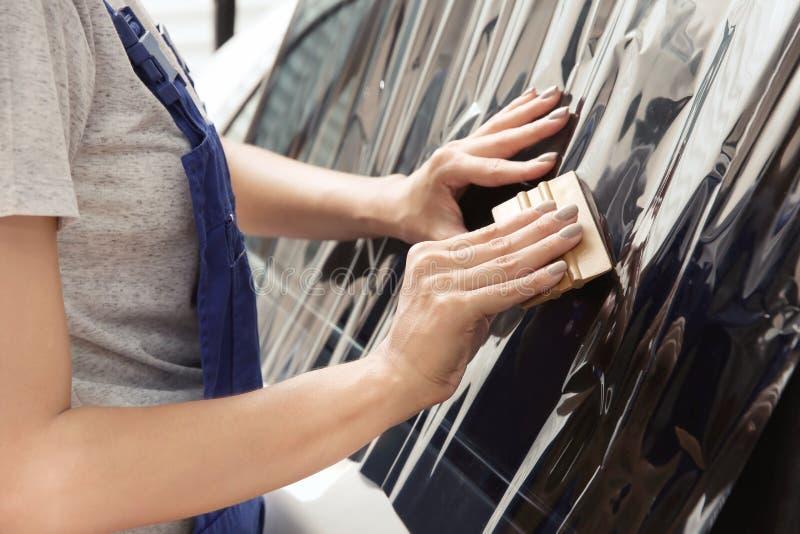 Kvinnlig arbetare som applicerar tona folie på bilfönster royaltyfria foton