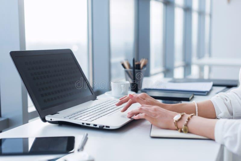 Kvinnlig arbetare som i regeringsställning använder bärbara datorn och att arbeta med nytt projekt Kvinna som hemma blogging som  arkivbild
