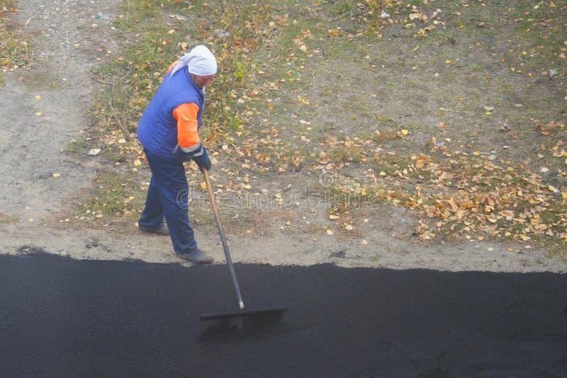 Kvinnlig arbetare under att asfaltera vägen Tungt kvinnligt manuellt arbete i konstruktion arkivfoton