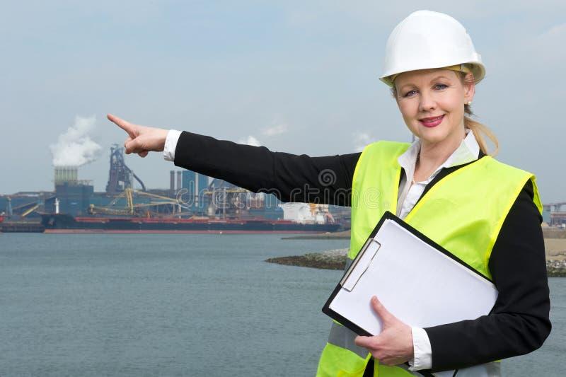 Kvinnlig arbetsledare i hardhat och säkerhetsväst som pekar till den industriella platsen royaltyfria foton
