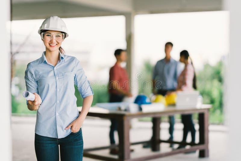 Kvinnlig arkitekt eller tekniker med ritningen på byggnadskonstruktionsplatsen Coworkermöte på suddighetsbakgrund royaltyfria bilder