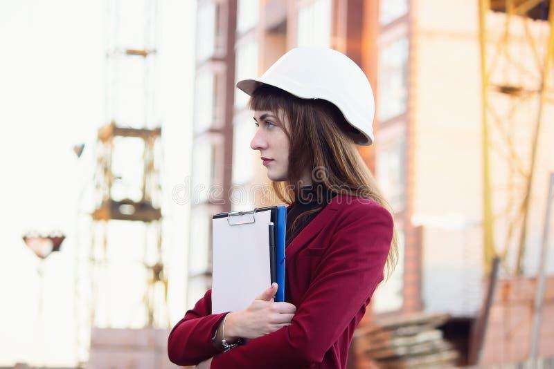 Kvinnlig arkitekt- eller teknikerinnehavritning och bärande vit säkerhetshjälm på bakgrund för byggnadskonstruktion royaltyfri foto