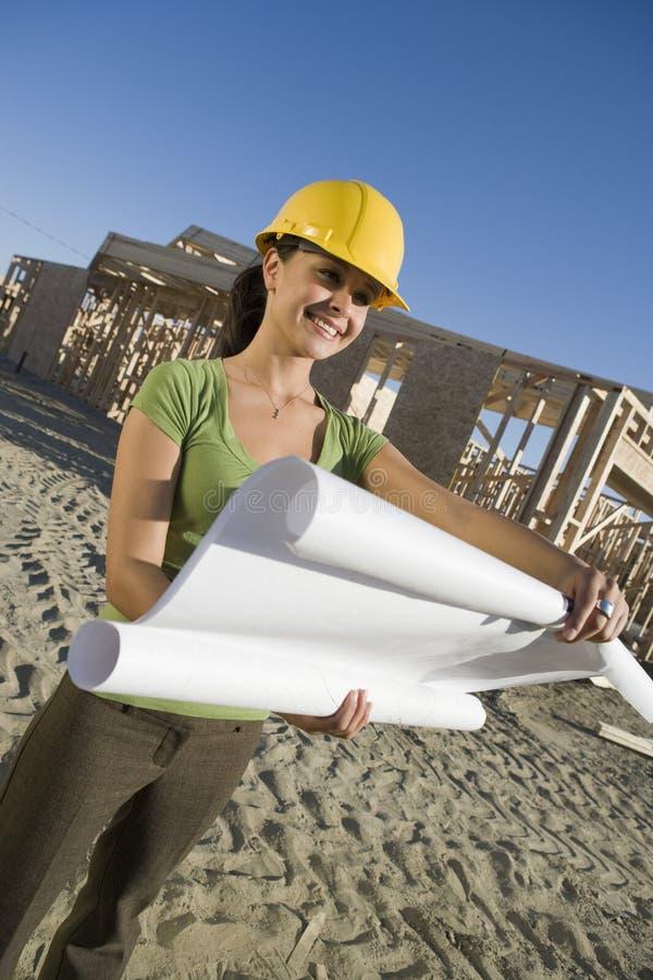 Kvinnlig arkitekt Holding Blueprint royaltyfria foton