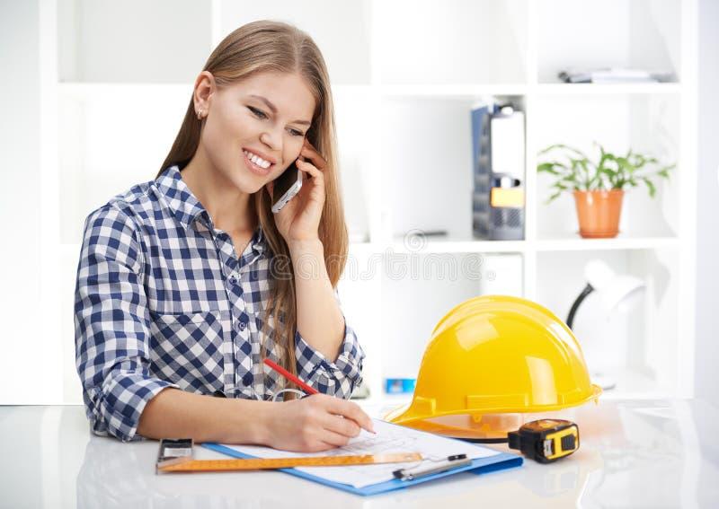 Kvinnlig arkitekt med telefonen royaltyfri bild