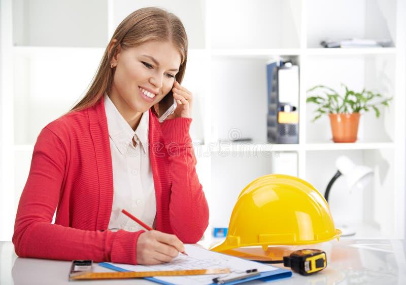 Kvinnlig arkitekt med telefonen royaltyfri foto