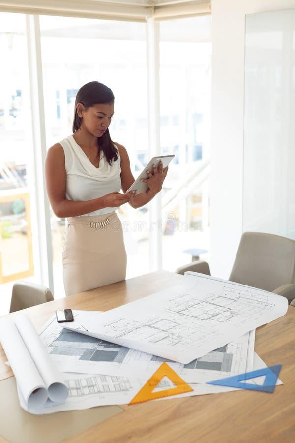Kvinnlig arkitektur genom att använda den digitala minnestavlan på tabellen i ett modernt kontor arkivbilder