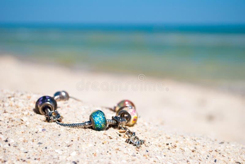 Kvinnlig armbandgarnering ligger på sanden på en bakgrund av det blåa havet och blå himmel royaltyfri bild