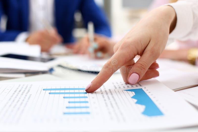 Kvinnlig armpunktpinger i finansiell graf fotografering för bildbyråer