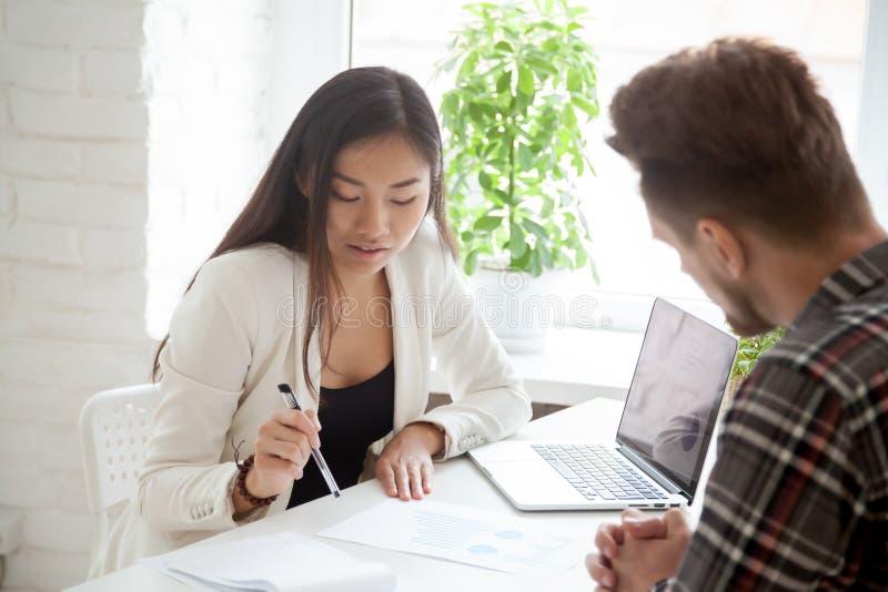 Kvinnlig asiatisk arbetsledare som förklarar finansiella grafer till manlig coll arkivfoto