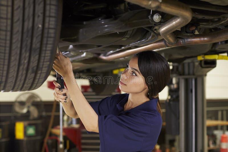 Kvinnlig auto mekaniker Working Underneath Car i garage arkivbilder