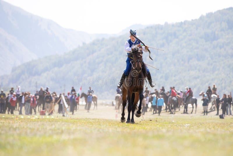 Kvinnlig bågskytt som skjuter en pil på hästrygg arkivfoton