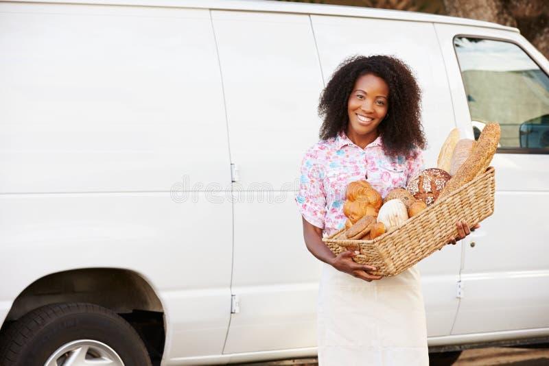 Kvinnlig bagare Delivering Bread Standing i Front Of Van arkivfoton