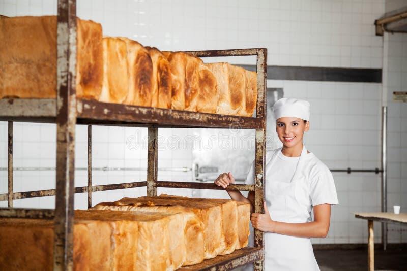 Kvinnlig bagare Standing By Rack med nytt bakade bröd fotografering för bildbyråer
