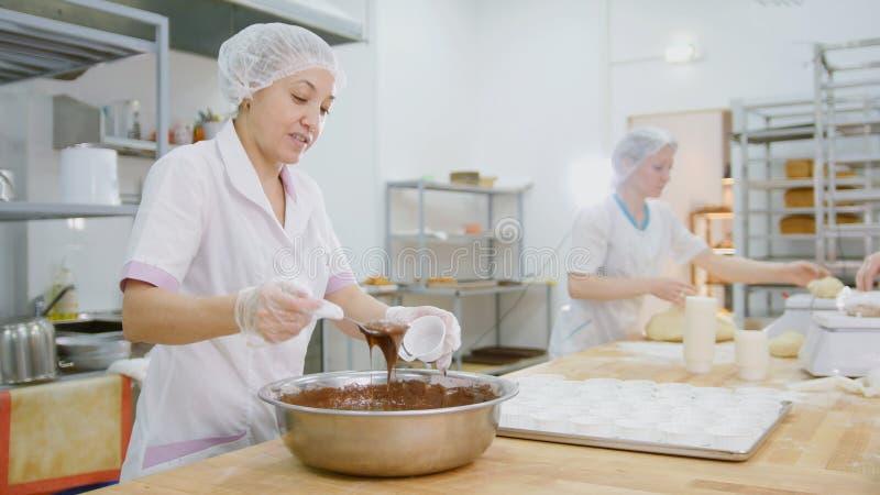 Kvinnlig bagareblandningchokladpralin i metallbunke och danande bakar ihop royaltyfri foto