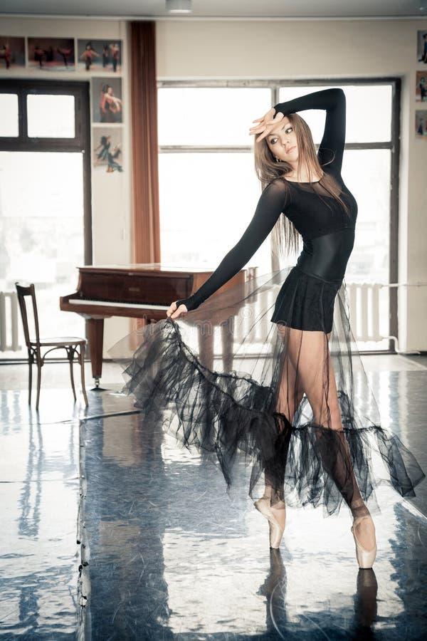 Kvinnlig balettdansör som poserar på en toptoe i en dansgrupp royaltyfria bilder
