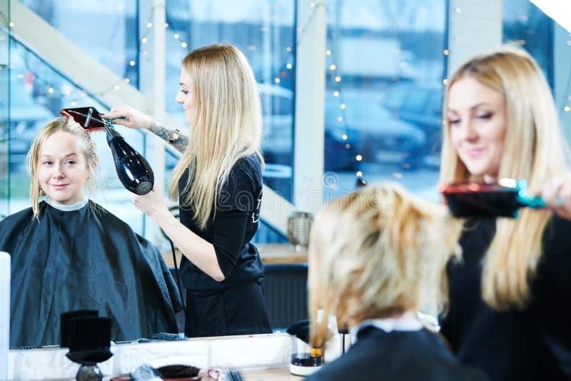 Kvinnlig barberare med frisyr för hårtorkdanandeman arkivbild
