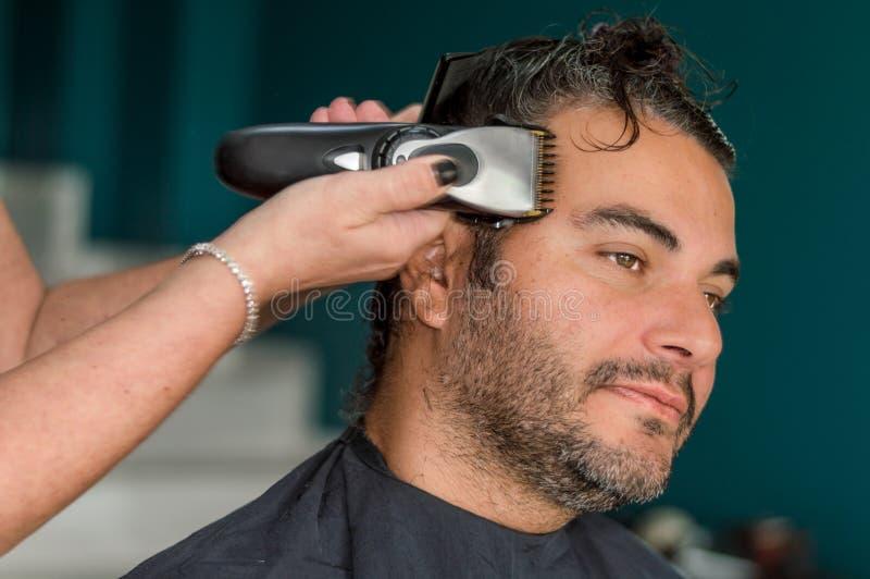 Kvinnlig barberare som arbetar med hårclipperen som rakar ung mans framsida arkivbild