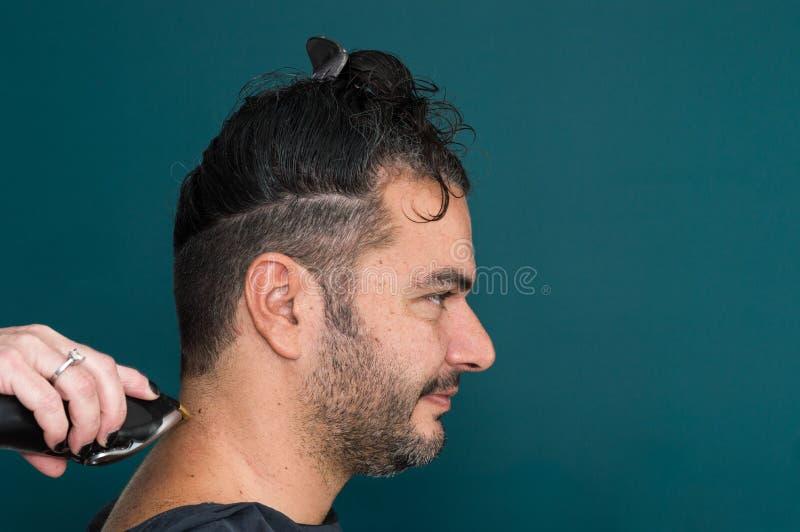 Kvinnlig barberare som arbetar med hårclipperen som rakar ung mans hals royaltyfria bilder