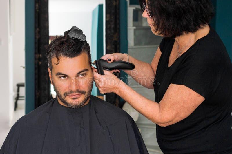Kvinnlig barberare som arbetar med hårclipperen som rakar ung mans huvud royaltyfri bild