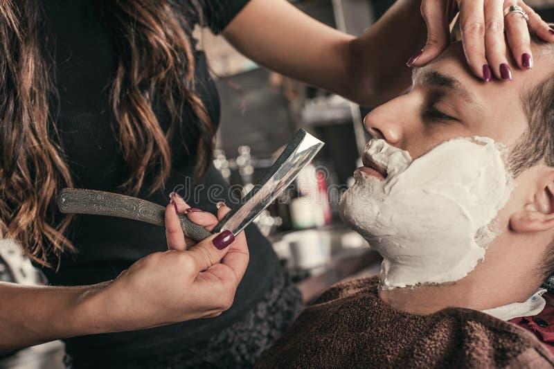 Kvinnlig barberare som rakar en klient fotografering för bildbyråer