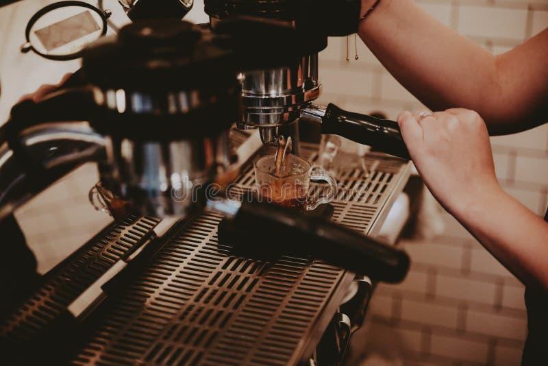 Kvinnlig barista genom att använda kaffemaskinen och göra en läcker latte arkivbild
