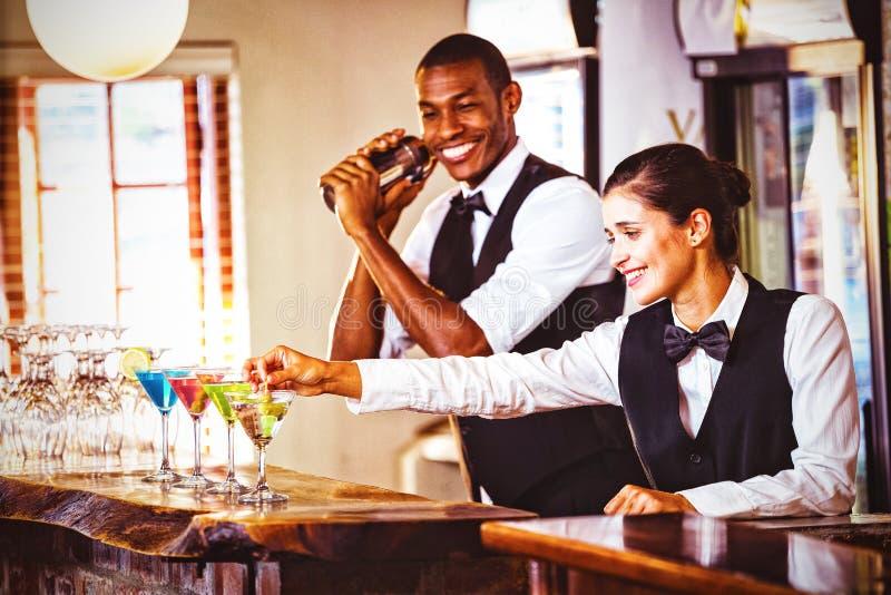 Kvinnlig bartender som garnerar coctailen med oliv royaltyfri foto